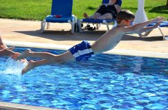 A young Caucasian boy jumping into a pool on vacation in a tropical destination Royalty Free Stock Photo