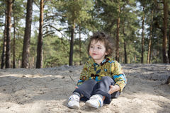 In the summer of funny little girl sitting on the ground in a pi Royalty Free Stock Images