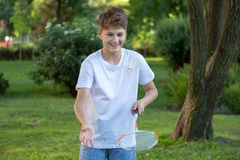 Summer funny portrait of cute boy kid playing badminton in green park. Healthy lifestyle stock images