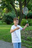 Summer funny portrait of cute boy kid playing badminton in green park. Healthy lifestyle stock photo