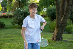 Summer funny portrait of cute boy kid playing badminton in green park. Healthy lifestyle royalty free stock image