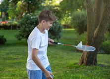 Summer funny portrait of cute boy kid  playing badminton in green park. Sport, Healthy lifestyle royalty free stock image