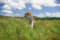 Summer game. Happy child run on the field with red poppies Royalty Free Stock Image