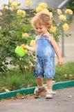 Summer garden. Smiling child in spring garden with roses royalty free stock photos