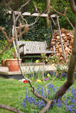 Summer garden. Relaxing summer garden back yard with flowers and a swing bench Royalty Free Stock Photography