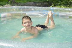 In the summer in the garden boy bathes in inflatable pool. Stock Image