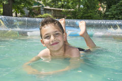 In the summer in the garden boy bathes in inflatable pool. Royalty Free Stock Photo