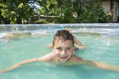 In the summer in the garden boy bathes in inflatable pool. Royalty Free Stock Photography