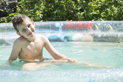 In the summer in the garden boy bathes in inflatable pool. Stock Photos