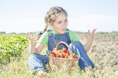 In summer, in the garden, a small sweet curly girl eats strawberries. royalty free stock images