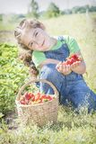 In summer, in the garden, a small sweet curly girl eats strawberries. stock photo
