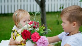 Summer, in the garden. The four-year-old boy gives a bouquet of flowers to his younger one-year-old sister, the girl stock video