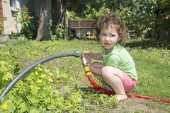 In summer, the garden includes a little girl with a hose tap. Stock Photo
