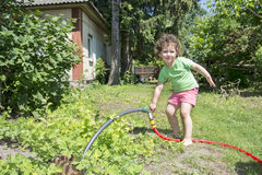 In summer, the garden includes a little girl with a hose tap. royalty free stock image