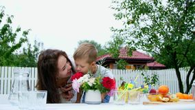Summer, in the garden. Mom with a four-year-old son make a bouquet of flowers. The boy likes it very much, having fun stock video
