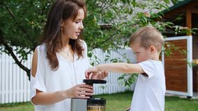 Summer, in the garden. Mother and four-year-old son make fresh juice of mandarins, put mandarin slices in a juicer stock footage