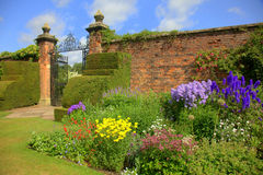 Summer garden with old wall and gates. Wall garden with metal gates and topiary shrubs in English Stately Home Royalty Free Stock Image
