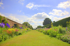 Summer garden with old wall and gates. Perspective of the walled garden at an  English Stately Home Royalty Free Stock Photo