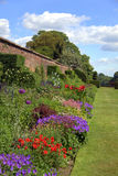 Summer garden with old wall and gates. Wall garden with gates and topiary shrubs in English Stately Home Stock Photo