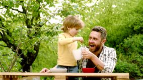 Summer garden party Father with son. Happy father with his son sitting on the table eating healthy food with funny. Expression on face. Small boy enjoy stock video