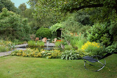 Summer Garden with a Pond. Beautiful garden with a pond. In the foreground, a relax feauteuil Stock Photos