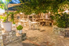 Summer garden restaurant. Empty tables and chairs in a mediterranean stone garden restaurant royalty free stock photos