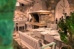 Summer garden restaurant. Empty tables and chairs in a mediterranean stone garden restaurant stock image