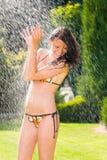 Summer garden smiling woman swimsuit splash water Stock Images