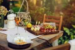 Summer garden table decorated with flowers and candles, evening party with wine. Cheese and fruits stock images