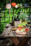 Summer garden table with wine and fruits in the evening. On old wooden table stock photo