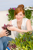 Summer garden terrace redhead woman potted flower Royalty Free Stock Images