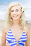 Summer Girl. Lovely Summer Girl Half Body Portrait With Floral Decoration In Her Blond Hair Standing Outdoors At A Beach Location Wearing Blue Striped Swimming Royalty Free Stock Images