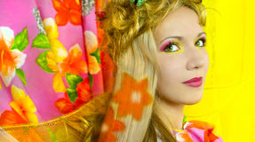 Summer girl. Young girl with pink and yellow makeup and hair colouring in the shape of flowers royalty free stock photo
