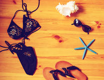 Summer girl accessories on wooden background top view. Toned. Stock Photography
