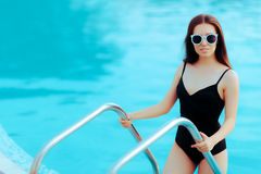 Summer Girl with Fashion Sunglasses and Black Swimsuit by the Pool. Portrait of a stylish woman in bathing suit Stock Photo