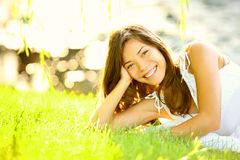 Summer girl in grass. Smiling happy. Lifestyle image of beautiful young woman in summer dress lying joyful in park on sunny sunshine day. Mixed race Caucasian Royalty Free Stock Image