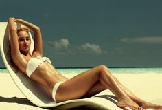 Summer girl model with tanned body. Posing in the white cha. Ir on the beach of the tropical island royalty free stock photography