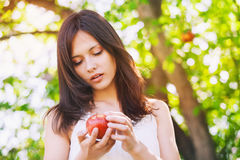 Summer girl on nature with fresh apple in hands. Stock Photography