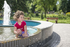 In the summer, girl play in the fountain in the park. Royalty Free Stock Photos