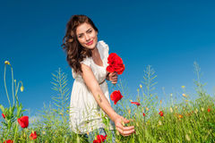 Summer girl in poppy field holding a poppies bouquet Stock Photo