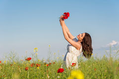 Summer girl in poppy field holding a poppies bouquet Royalty Free Stock Images
