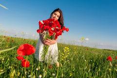 Summer girl in poppy field holding a poppies bouquet Royalty Free Stock Photography