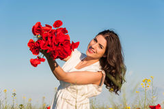 Summer girl in poppy field holding a poppies bouquet Royalty Free Stock Photo