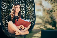 Summer Girl Reading a Novel Outdoors in Nest Chair Stock Photography