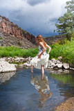 Summer girl by the river. Beautiful young woman walking in water by the river Royalty Free Stock Photo