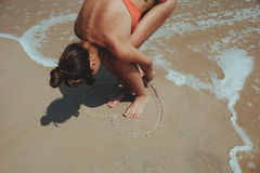 Summer girl sea.  Teenager draw heart on sand. Stock Image