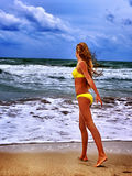 Summer girl sea in yellow swimsuit. Summer girl sea. Girl in swimsuit on beach near ocean with waves. Sea summer holiday Stock Photos