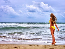 Summer girl sea in yellow swimsuit. Summer girl sea. Girl in swimsuit on beach near sea with waves Royalty Free Stock Image
