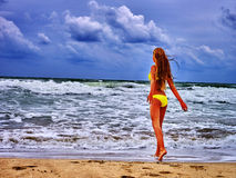 Summer girl sea in yellow swimsuit. Summer girl sea. Young girl in swimsuit on beach near ocean with waves. Girl goes beach and admiring waves Royalty Free Stock Image