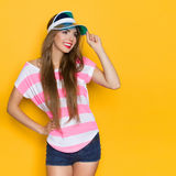 Summer Girl In Sun Visor Cap. Smiling young woman in pink stripped shirt and blue sun visor posing with hand on hip and looking away. Three quarter length studio Stock Images